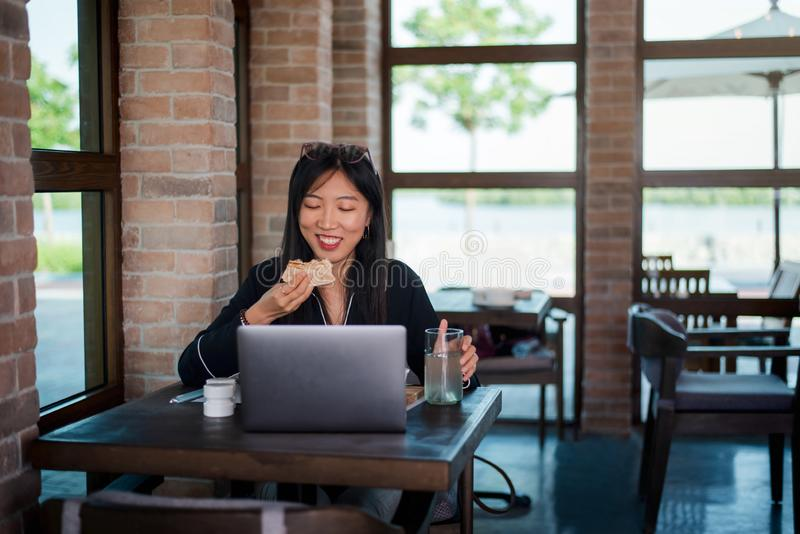 Girl working and having a meal. Girl working on laptop and having a quick snack woman bar cafe eat eating toast bite restaurant freelance fast lunch break stock photos