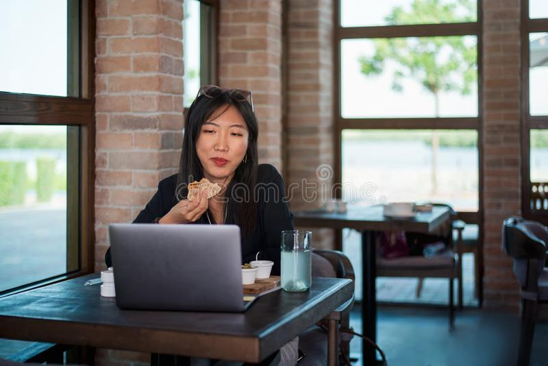 Girl working and having a meal. Girl working on laptop and having a quick snack woman eating asian restaurant bar cafe toast bite freelance female fast learning royalty free stock image