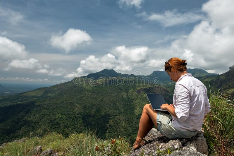 Girl working on her computer on the top of the mountain. royalty free stock image