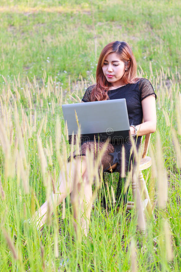 Girl working on her laptop computer outside. On the chair in park royalty free stock image