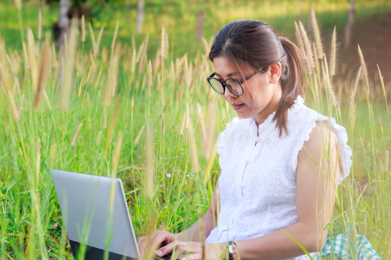 Girl working on her laptop computer outside. On meadow stock photography