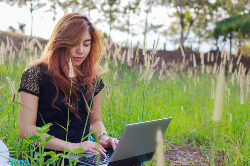 Girl working on her laptop computer outside on meadow grass. Asian girl working on her laptop computer outside on meadow grass royalty free stock photography