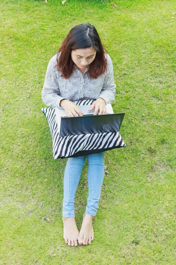 Girl working on her laptop computer outside. In park stock photography
