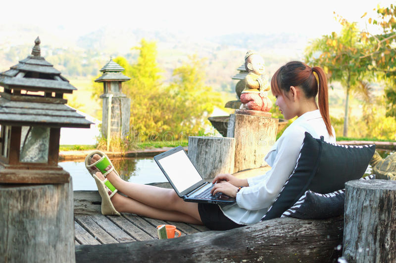 Girl working on her laptop computer outside. On the park royalty free stock photos