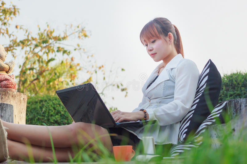 Girl working on her laptop computer outside. On the park stock photography