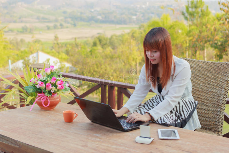 Girl working on her laptop computer outside. On the terrace stock photo