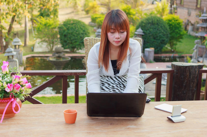 Girl working on her laptop computer outside. On the terrace royalty free stock photo