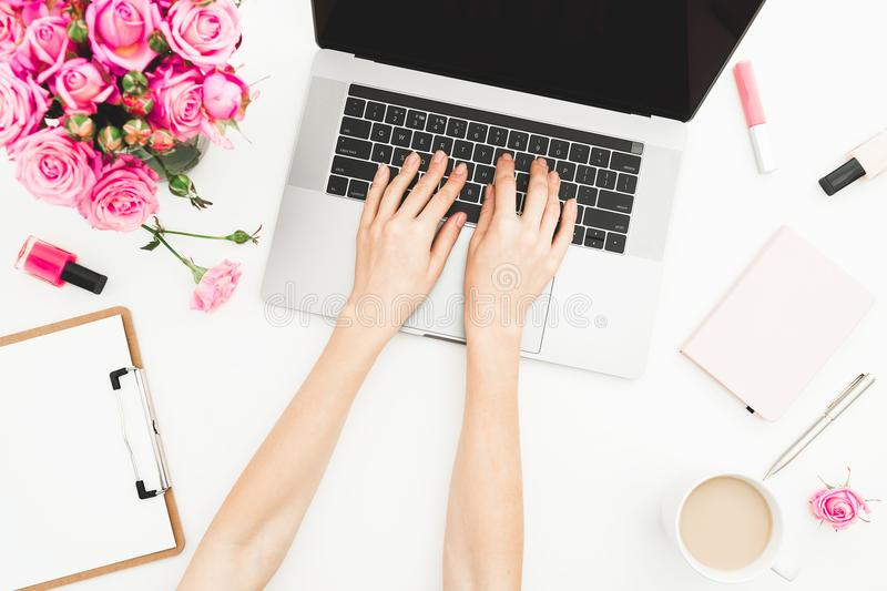 Girl working on laptop. Woman workspace with female hands, laptop, pink roses bouquet, accessories, diary on white background. Top royalty free stock image