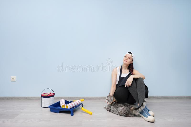 Girl working, painter, sitting on the floor and looking at the wall. He chooses, thinks, rests, next to him goes a pet stock photography