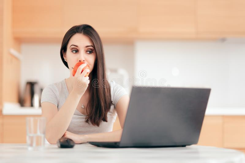 Woman Eating an Apple While Working on Laptop stock image