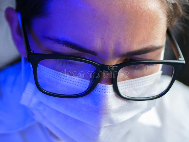 The girl works in the DNA laboratory. A young female technician or scientist works in a laboratory. Close-up stock image