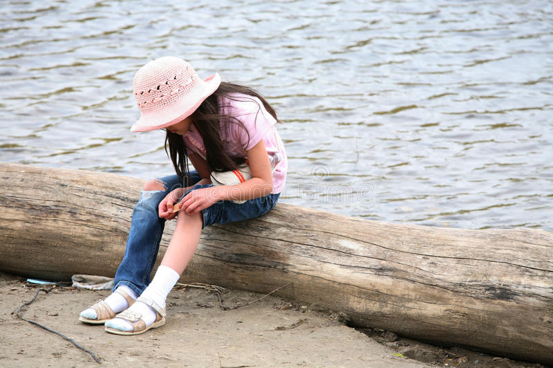 Download Girl With Wound Sitting On Log Stock Image - Image: 9572871