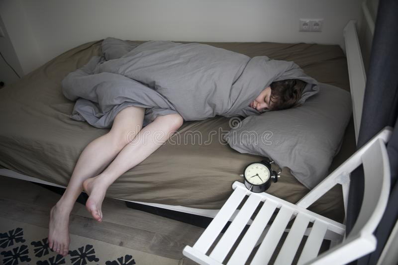 Girl, wrapped in a grey blanket, puts out her hand to turn off the alarm. There is six hours on the alarm clock royalty free stock images