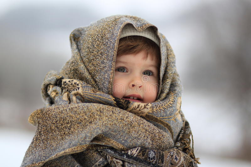 The girl is wrapped up in a scarf. The girl in a scarf in the winter on walk stock photography