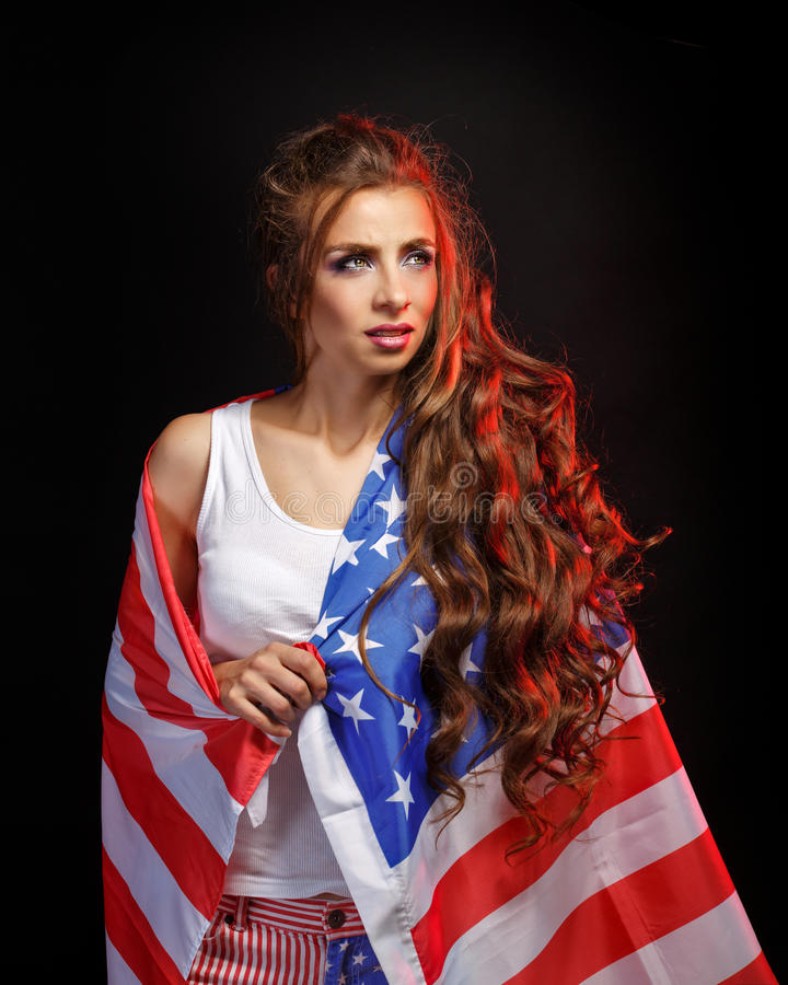 Girl wrapped in a US flag. Young attractive girl wrapped in a US flag. She a T-shirt and shorts with a print of the flag. Long curly hair. Portrait of a real stock images