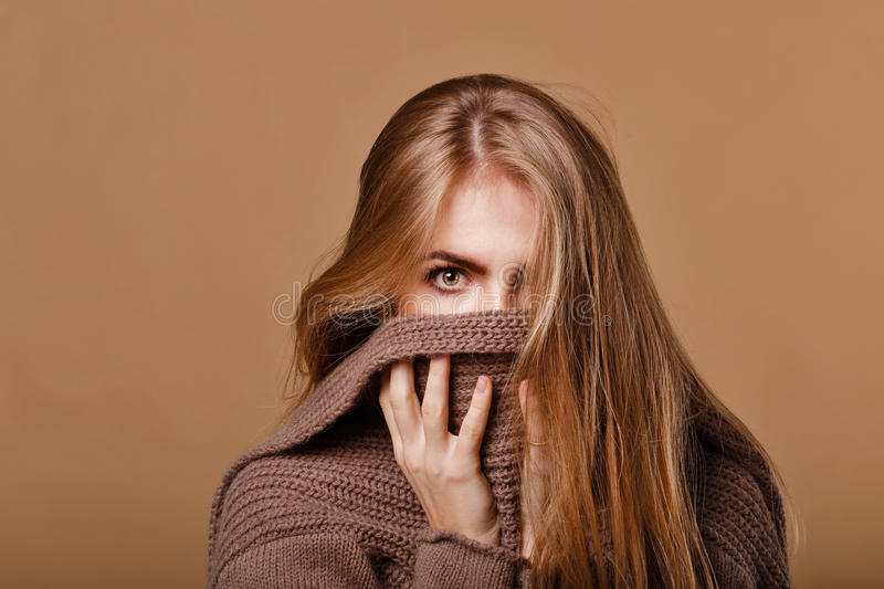 Girl wrapped in a warm sweater. We see only the eyes. royalty free stock photography