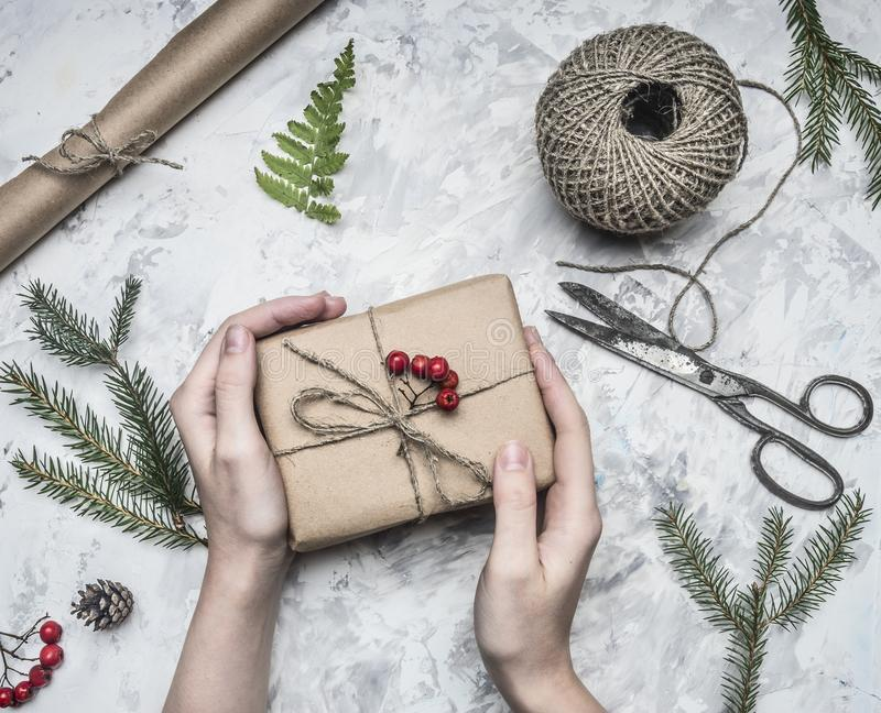 Girl wraps a gift for new year or Christmas, next to it is a roll of paper, vintage scissors, twigs Christmas trees and berri. Girl wraps a gift for a new year royalty free stock photo
