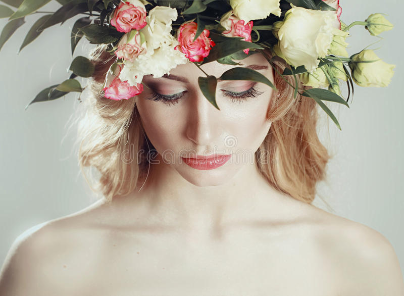 Girl with a wreath of flowers on her head on white background.  royalty free stock photo