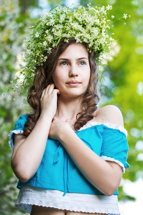 Girl with a wreath of wild flowers. girl of European appearance with a wreath in the garden royalty free stock photography