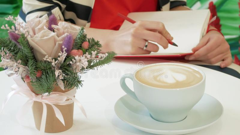 Girl writer creates a new work in a cafe with a pencil in a red notebook. On the background of painted green leaves royalty free stock photos