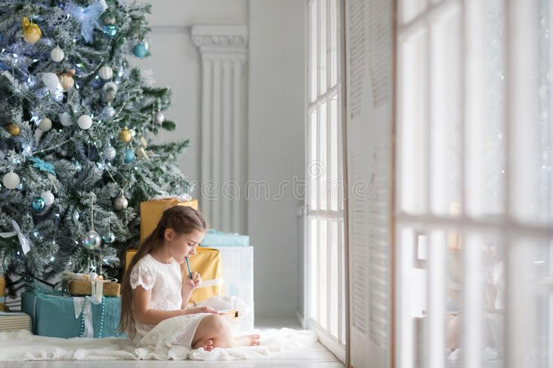 Girl writes a letter to Santa Claus in a large and bright room with a Christmas tree in blue and gold colors stock photography