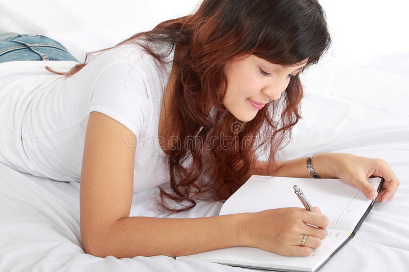 Download Girl Writing Book On The Bed Stock Photo - Image: 22568086