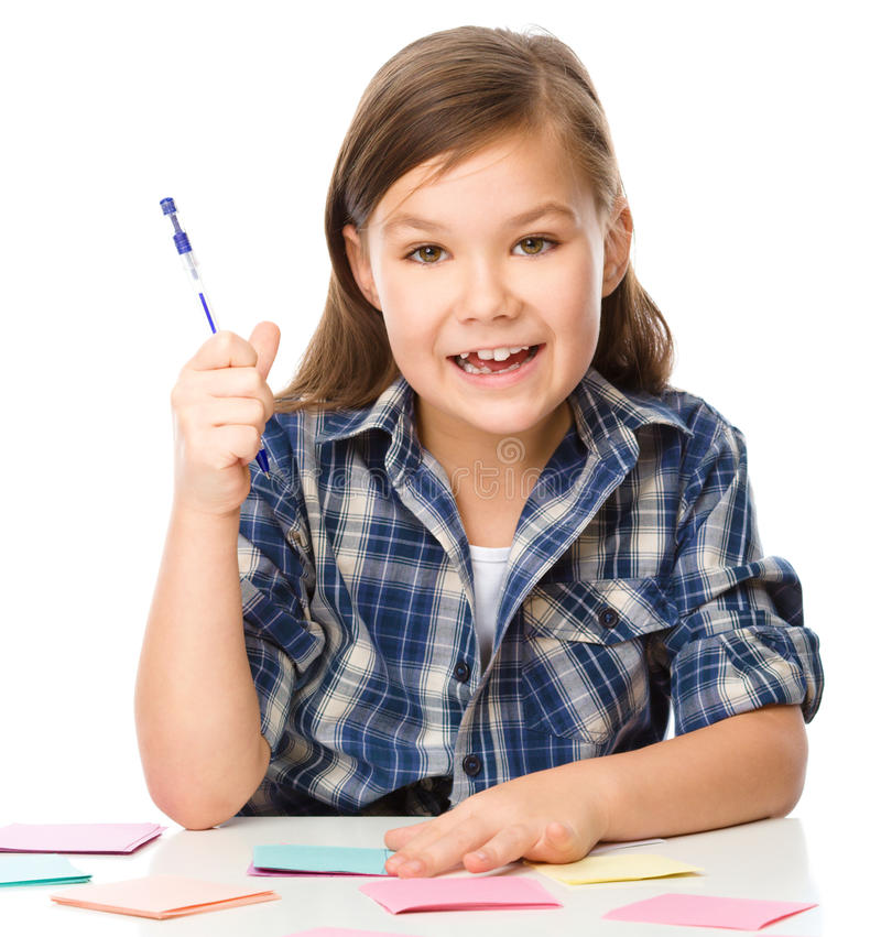 Girl is writing on color stickers using pen. Planning concept, self-organization, isolated over white stock photography