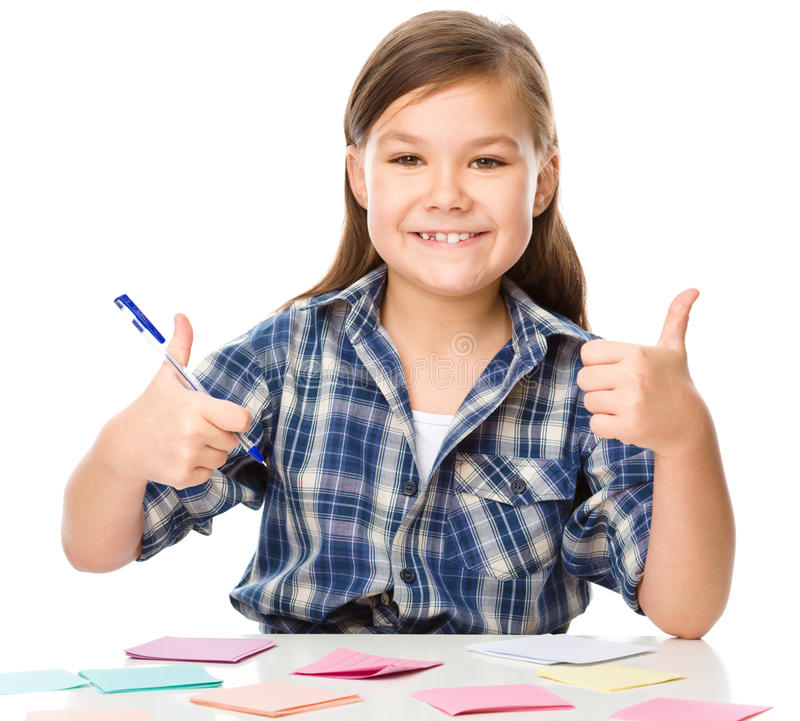 Girl is writing on color stickers using pen. Planning concept, self-organization, showing thumb up sign, isolated over white royalty free stock photos