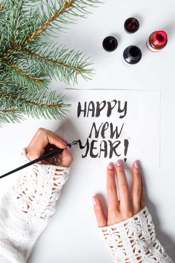 Girl writing Happy new year calligraphy card. Top view royalty free stock photos