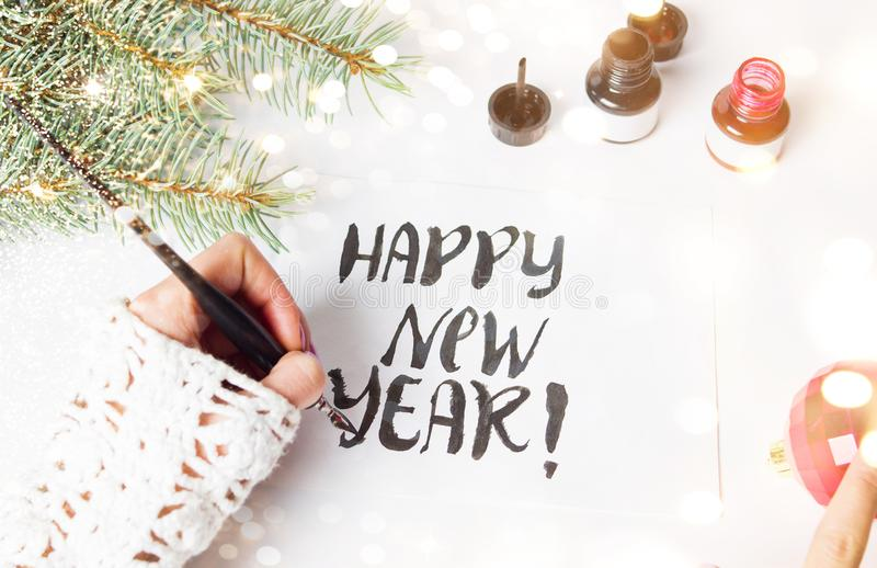 Girl writing Happy new year calligraphy card. Top view stock image