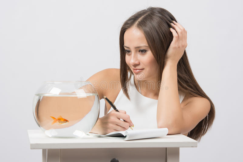 Girl writing in a notebook and looking at a goldfish in an aquarium. A young girl sits next to a round aquarium in which swimming goldfish stock photography