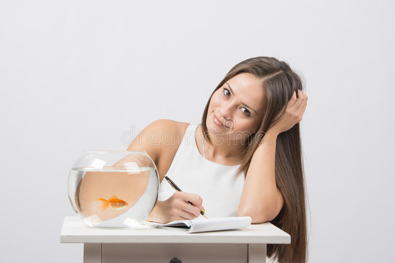 Girl writing in a notebook, standing next to an aquarium with goldfish. A young girl sits next to a round aquarium in which swimming goldfish royalty free stock photos