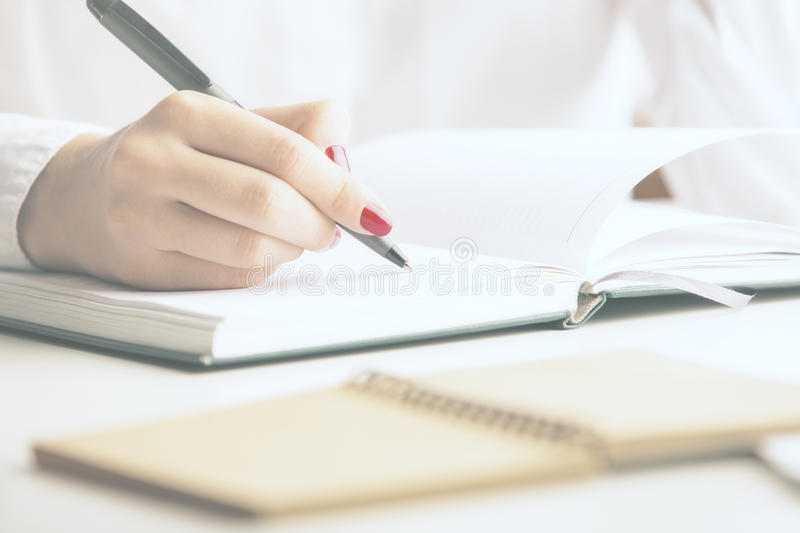Girl writing in notepad. Close up of girl`s hand writing in notepad placed on desktop with other items stock photo