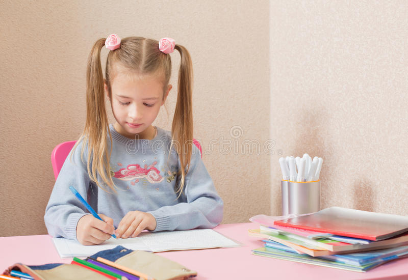 Girl writing with pen at the table royalty free stock images