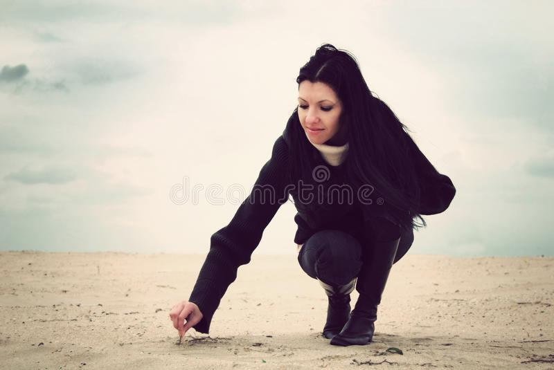 Girl writing in the sand stock images