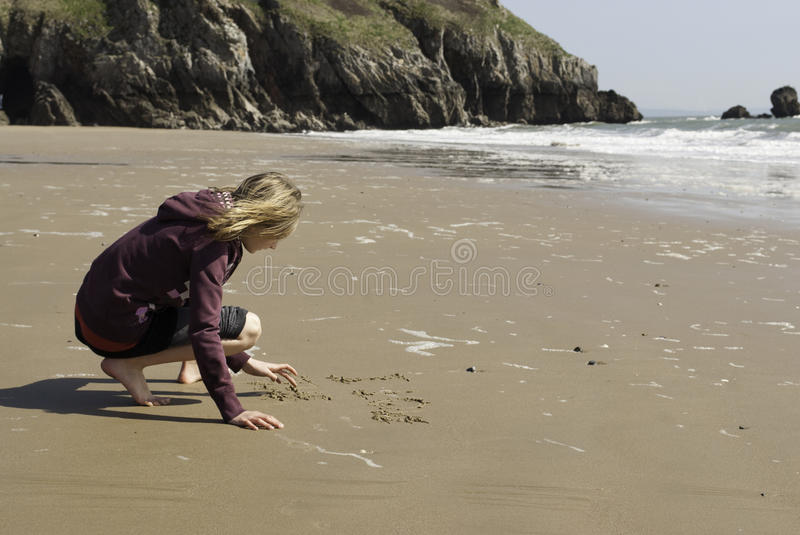 Girl Writing in the Sand on the Beach stock images