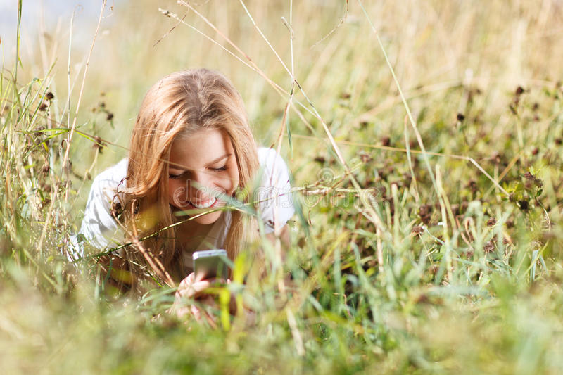 Download Girl Is Writing Sms On The Phone Lying In Grass Stock Image - Image of cellphone, lying: 33051141