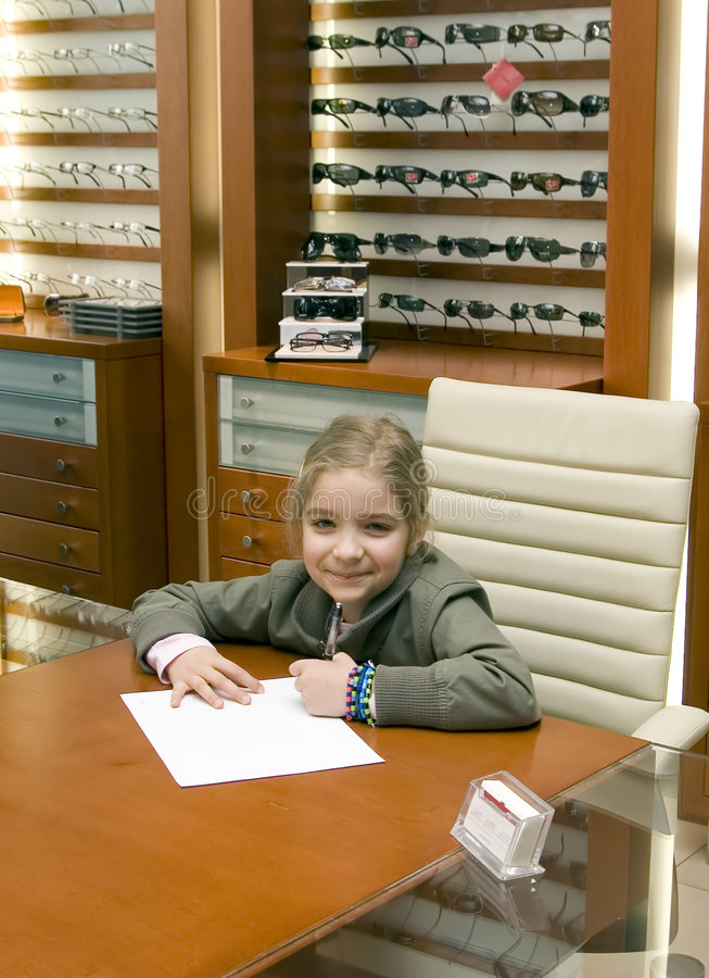 Girl writing at table. A young girl writing on paper at a table in an eyeglass store royalty free stock photo