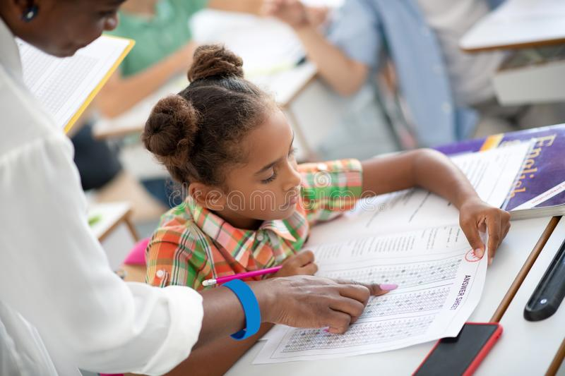 Dark-skinned schoolgirl looking at her answer sheet while writing test royalty free stock image