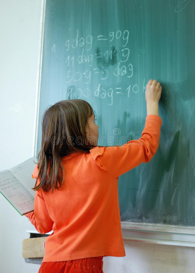 Girl writting on the school board royalty free stock photography