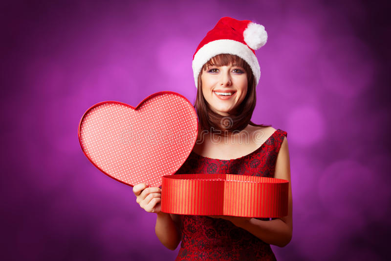 Girl in xmas hat with gift box. On violet background stock images
