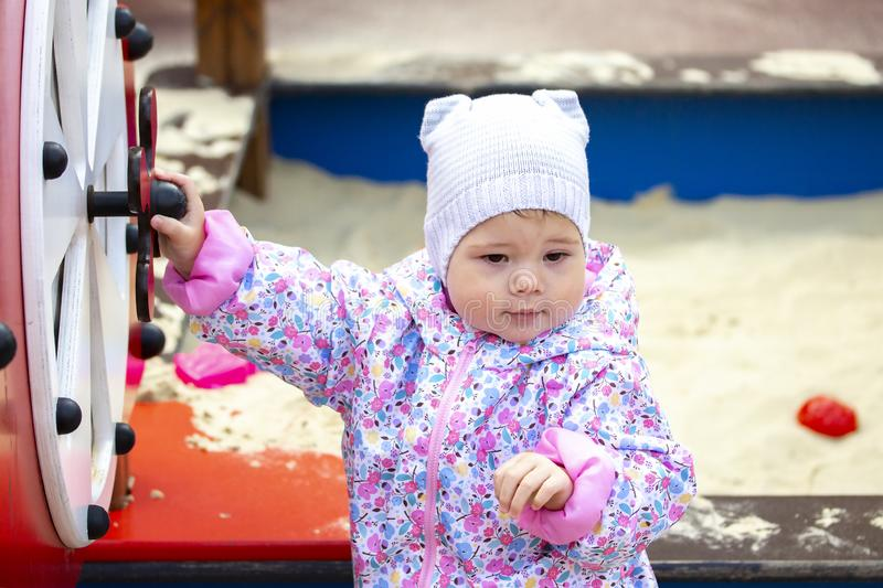 Girl 1 year walks on the playground, playing with children`s sports equipment. Baby jacket with flowers and a gray knitted hat fo. R a walk. independent girl royalty free stock image