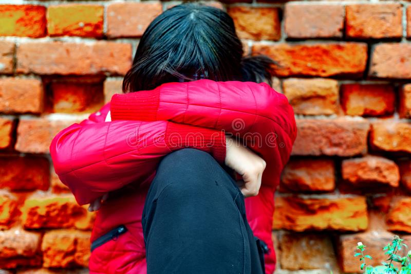 A girl, 13 years old, of the European race, in a red jacket against a brick wall, hid her face with her hands on her knees. An orphan child, psychological stock photography