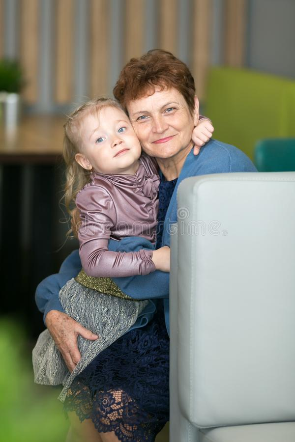 Little granddaughter tightly hugs her grandmother. stock image