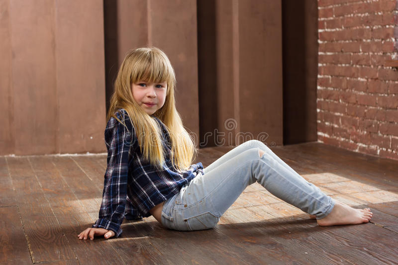 Girl 6 years old in jeans sitting on floor royalty free stock images