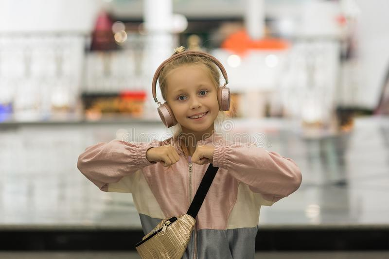 Girl of 9 years old listen to music in wireless headphones. Dancing girl. Cute child enjoying happy dance music royalty free stock images