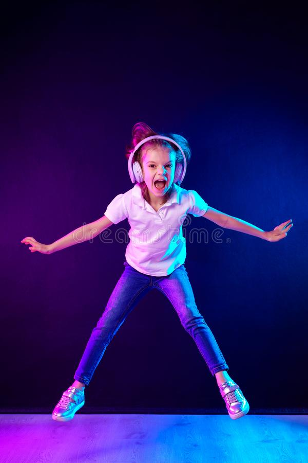 Girl listening to music in headphones on dark colorful background . Dancing girl. Happy small girl dancing to music. Girl of 7 years old listening to music in stock photography