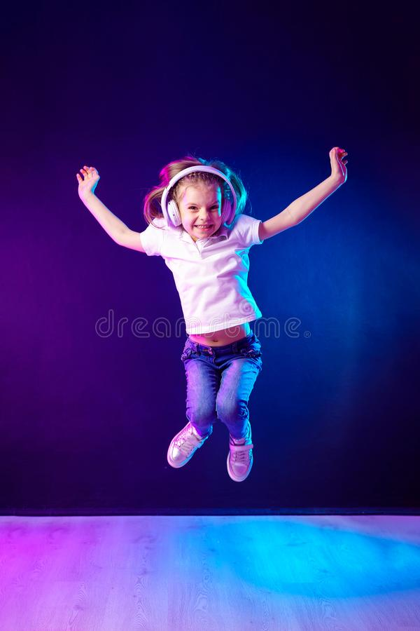 Girl listening to music in headphones on dark colorful background . Dancing girl. Happy small girl dancing to music. Girl of 7 years old listening to music in stock images
