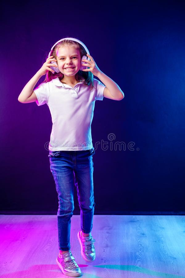Girl listening to music in headphones on dark colorful background . Dancing girl. Happy small girl dancing to music. Girl of 7 years old listening to music in stock image