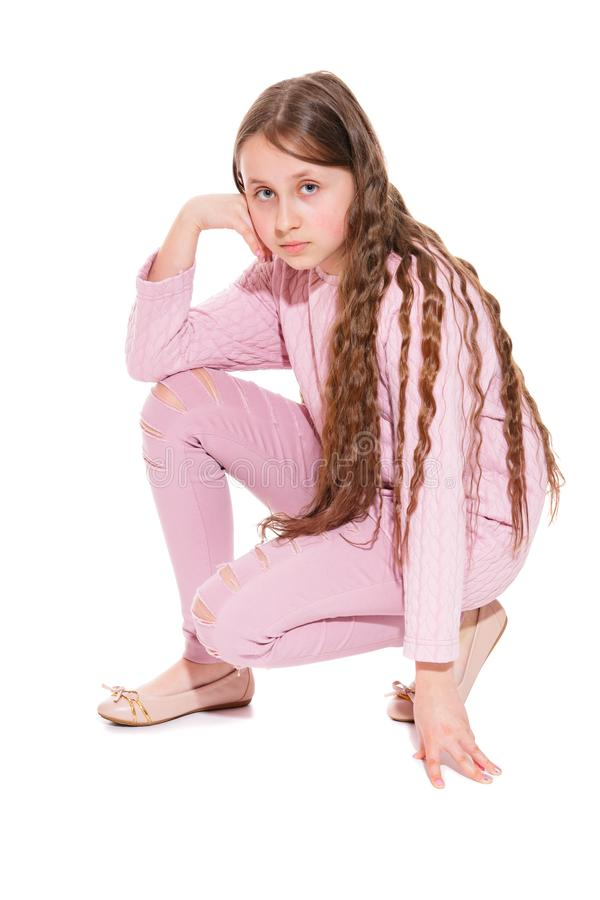 A girl of 10-11 years old with long beautiful hair sat on one knee. Isolation on a white. stock images